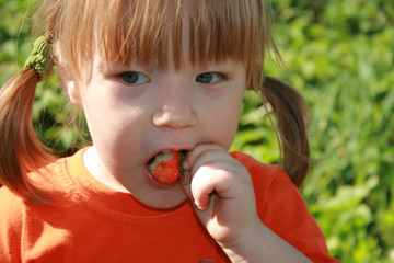 A little cute girl eating an strawberry..