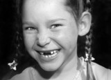 Young freckle faced toothless girl in braids laughing happily poster