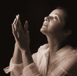 Woman with hands folded in prayer, looking up to the Light