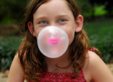 Young girl outside blowing bubble with gum poster