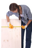 woman carpenter with wooden plank and measuring tape poster