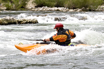 whitewater kayaker surfing a wave on grade 3 rapid