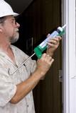 Elderly contractor caulking around glass door frame poster