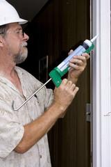 Elderly contractor caulking around glass door frame
