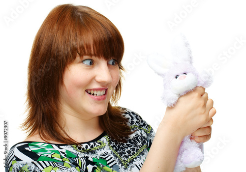 Angry young girl with toy bunny over white