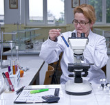 Female researcher looking at a test tube poster