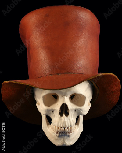 A Human Skull Wearing A Leather Tophat On Black
