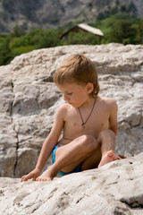 a little boy sits on a rock in melting