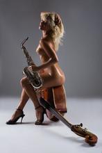 Mujer desnuda con el saxofón contrabajo sentado en un viejo