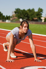 A pretty young woman exercising at the race track