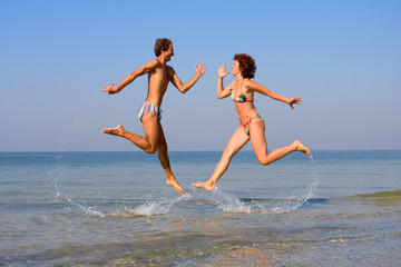 Smiling man and girl jumping at sea shoal with splashes