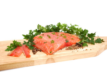 Raw salmon fillet on a wooden cutting board