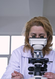 Female researcher looking through a microscope poster