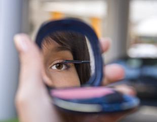 Mirror image of a woman's eye while she is applying mascara