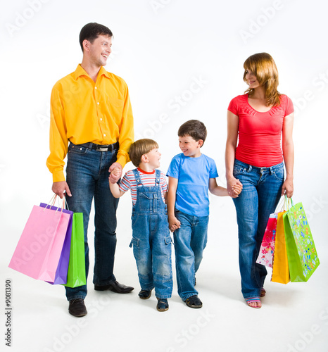 Photo of friendly family walking with shopping bags
