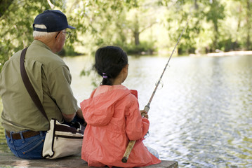 A young girl is fishing with her grandpa on a warm summer day.