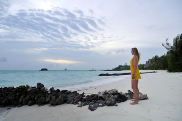 Sexy woman watching indian ocean in Maldives at sunset