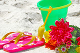 Colorful array of flip flops, pail, and flowers on beach poster
