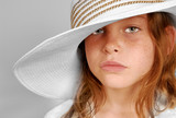 Young freckle faced girl with serious look wearing big hat poster