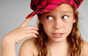 Young girl in plaid cap looking serious and thoughtful