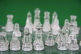 Translucent glass chess men on a green background