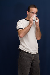 A sick young man blowing his nose