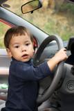 serious little boy driving a car poster