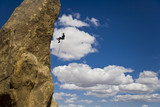 Climber rappelling from the summit of a rock spire. poster