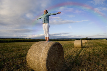 Girl standing in hay bale