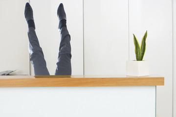 Businessman upside-down behind desk