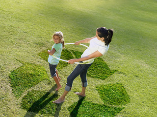 Mother and daughter hula hooping on recycling symbol