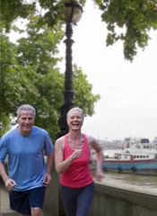 Mature couple running on waterfront
