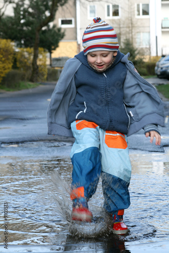 Little boy splashing in a mud puddle