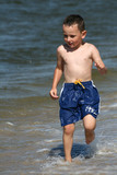 Boy  running in the water on the beach