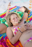Girls sunbathing and text messaging