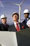 Businessmen inspecting wind power plant