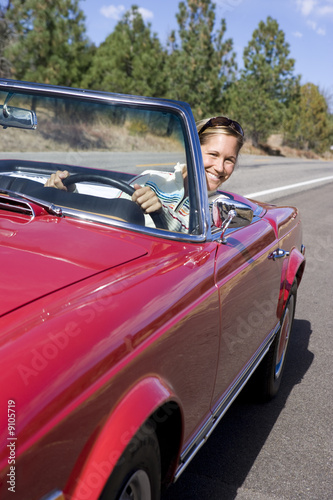 Women driving red convertible