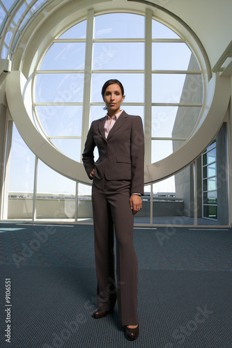 Businesswoman standing in front of round window