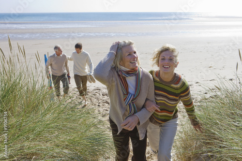 Four people walking on beach