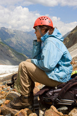 mountaineer girl sitting on backpack and looking to mountains