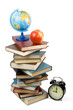 Pile of books, alarm clock and apple on a white background.
