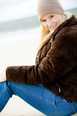 A young attractive woman outside on a beach in winter wear