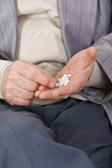 Close-up image of a senior's hands taking pills.
