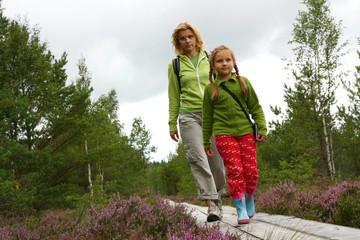 Mother and daughthter walking on  plank-way in forest