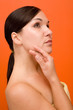 attractive and fresh brunette woman on orange background