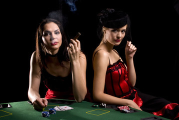 Two attractive woman playing poker and smoking cigarettes