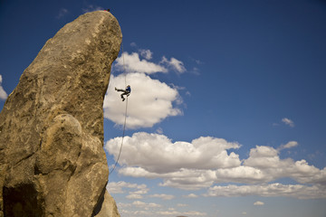 A climber rappells from the summit of a rock spire.