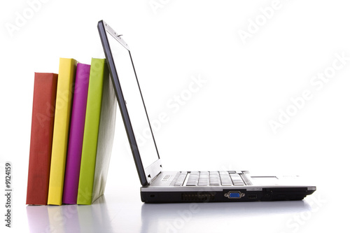 a laptop next to a stack of colorful books
