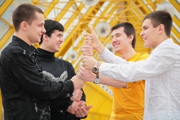 group of young men make piramid from hands
