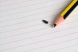 Pencil with a broken tip on a writing pad..